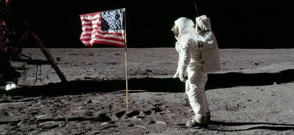 un homme sur la lune à côté du drapeau américain
